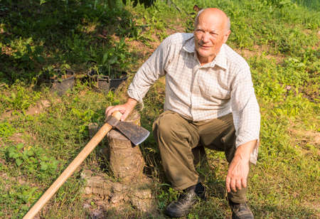 Smiling Senior man with the ax resting in the garden after the hard work.