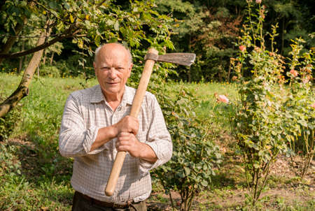 Portrait of elderly man with ax on his shoulder in the garden.