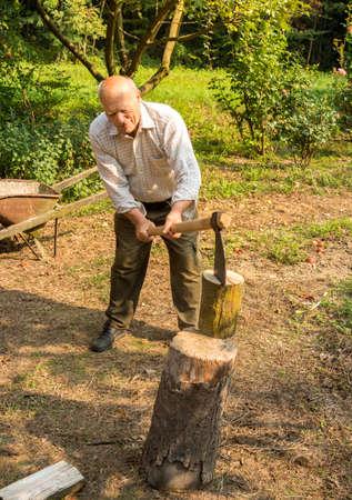 Senior man splitting wood with ax in the garden.