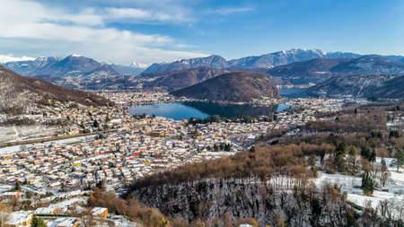 Aerial view of winter landscape of lake Lugano with Swiss Alps and village Cadegliano Viconago in province of Varese, Italy