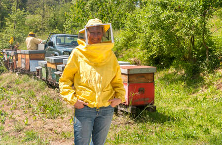 Portrait of smiling woman with beekeeping hat and veil in the garden.