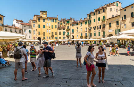 Lucca, Tuscany, Italy - July 3,2019: Amphitheater square with restaurants, bars and tourists in old town Lucca, Tuscany, Italy