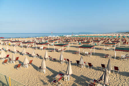 View of the Marina di Pietrasanta beach with white sand, umbrellas and chairs in the early morning in Versilia, Tuscany, Italy