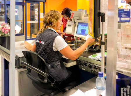 Riga, Latvia - September 8, 2019: European woman cashier working at the cash desk inside a Maxima supermarket in Riga, Latvia 新聞圖片