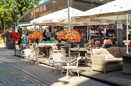 Riga, Latvia - September 5, 2019: People enjoying the street bar in a hot autumn sunny day in old Riga, Latvia