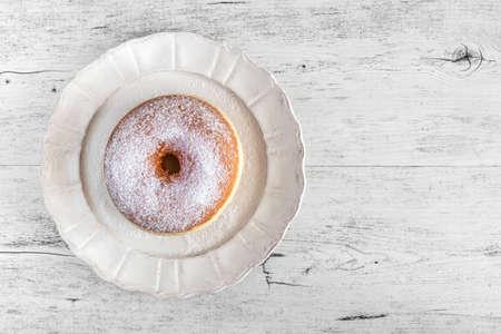 Buñuelo frito dulce cubierto con azúcar en un plato sobre el fondo de madera vieja.