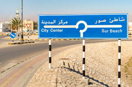 Street sign indicating the city center and the beach on the road in Sur, Sultanate of Oman. 스톡 콘텐츠