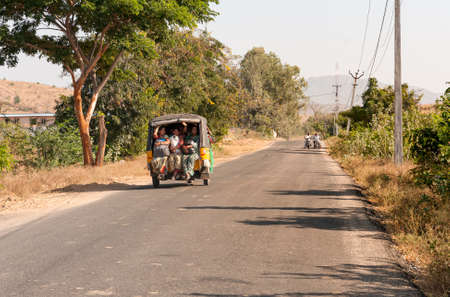 Puttaparthi, Andhra Pradesh, India - January 12, 2013: Indian women travel in rickshaw taxi along the road of Puttaparthi village, India