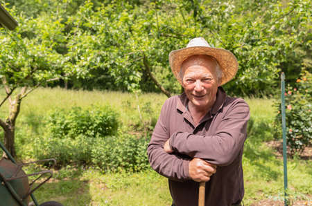 Portrait of smiling Elderly man wearing a hat in the his garden in springtime. 版權商用圖片 - 146920624