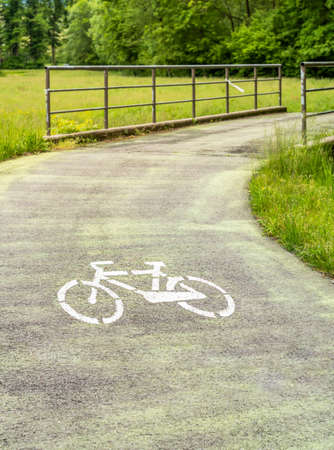 Green bicycle track with white sign on the floor.