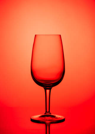 One Empty wine glass isolated on red background.