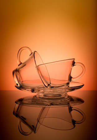 Two empty transparent coffee cup isolated on orange background. Standard-Bild