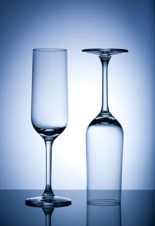 Two Empty wine glasses isolated on blue background. Standard-Bild