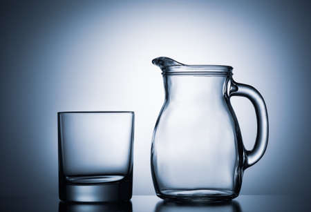 Empty water glass with water jug against blue illuminated background