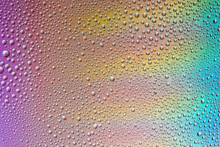 Background of water drops on gradient colorful surface.