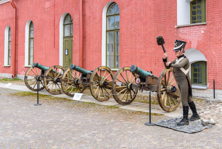 Saint Petersburg, Russia - June 17, 2015: Old artillery cannons in Naryshkin Bastion of Peter and Paul Fortress with wax statue of soldier in form of 19th century.