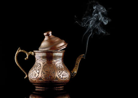 Ancient oriental copper teapot with white smoke isolated on a black background