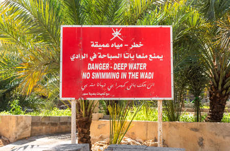 Danger - deep water and no Swimming sign in the Wadi, in Arabic and English language, Sultanate of Oman