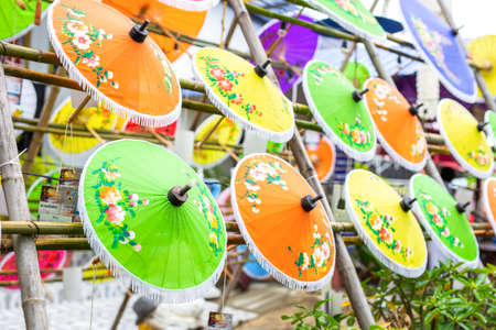 Colorful handmade paper umbrella hanging on top. Popular and famous on chiang mai