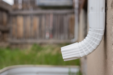 White gutter downspout and elbow