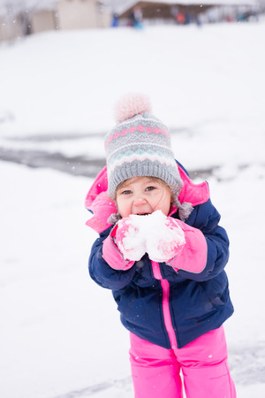 Little girl bundled up in pink and blue happily eating snow Stock Photo