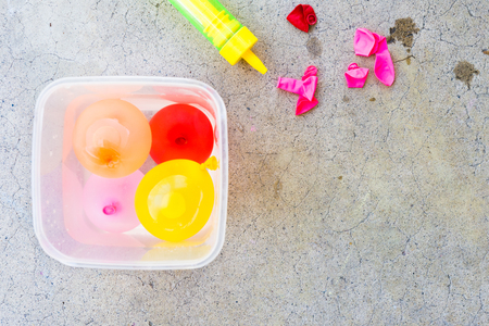 Overhead of small tub of water balloons and empty ones ready to be filled; open space for text