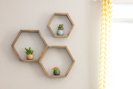 Three decorative wooden, floating, hexagon wall shelves, with decorative plants