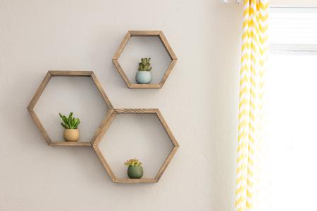 Drie decoratieve houten, zwevende, zeshoekige wandplanken, met decoratieve planten Stockfoto