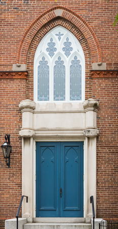 Tall decorative window arch over blue front church doors Stock Photo