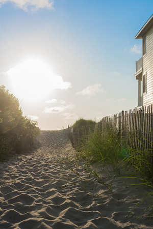 Beach access path with wooden barrier fence in the morning Stock Photo