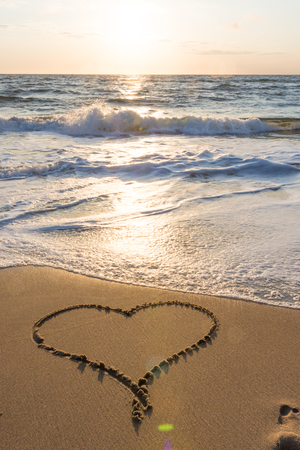 Heart drawn in the sand at beach sunset or sunrise