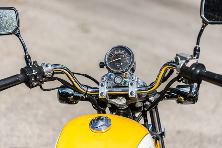 Closeup of restored antique motorcycle handlebar and controls