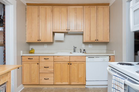 Clean light tan wood cabinets in small kitchen space