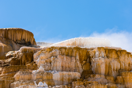 Waterfall over orange and white mineral deposits in Yellowstone National Park