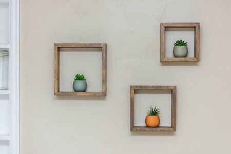 Square shaped floating shelves filling with colorful succulents