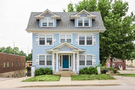 Dreistöckiges Kolonialhaus mit süßem hellblauem Abstellgleis auf kleinem Grundstück im Stadtgebiet Standard-Bild