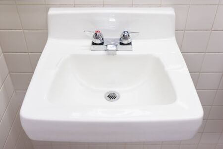 Front view of typical white porcelain bathroom sink in american public restroom