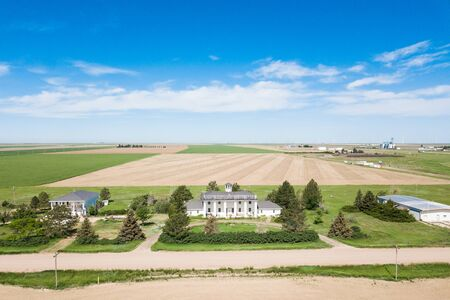 Historic white estate home in rural america, large expansive fields and blue sky