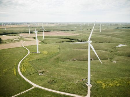 Drone shot of white wind turbines scattered across flat landscape