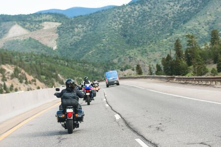 Group of motorbikes ride on interstate highway through mountain pass, Colorado United States Фото со стока