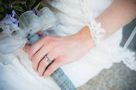 Bride shows off wedding ring, purple bouquet, veil and white wedding dress