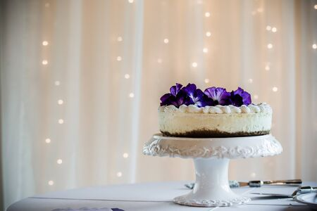 Non-traditional wedding cake, cheesecake with purple flowers on white pedestal