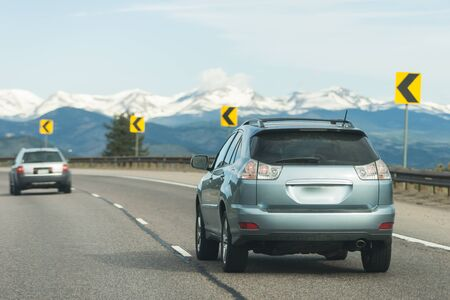 Sport utility vehicle driving on interstate highway going through snow capped mountain pass, steep turn