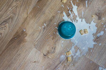 Céréales et lait détrempés renversés sur un plancher de bois franc en vinyle de luxe imperméable