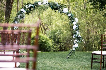 Wooden chairs and floral archway setup for outdoor wedding ceremony