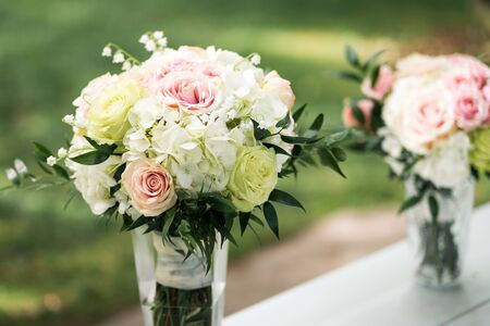 Floral bouquet of white, green and pink in vase before wedding ceremony