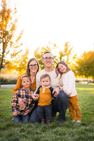 Young family of five take portraits at fall colored park