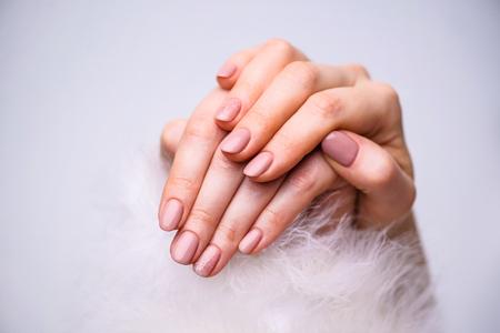 Nagels ontwerp. Handen Met Helder Roze Lente Manicure Op Een Grijze Achtergrond. Sluit Omhoog Van Vrouwelijke Handen. Kunst nagel.