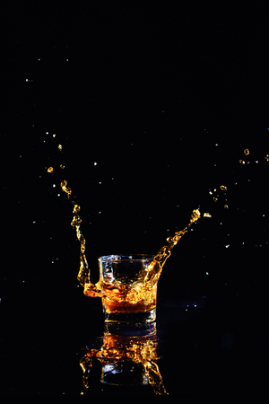 Isolated shot of whiskey with splash on black background, brandy in a glass 版權商用圖片 - 121161283