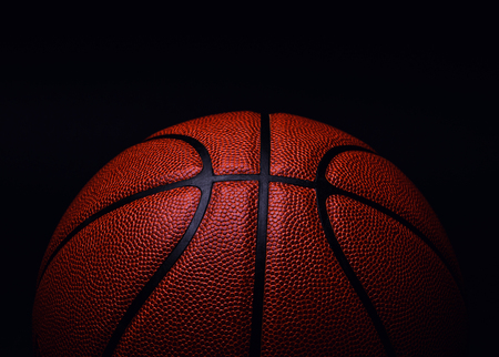 Basketballball auf schwarzem Hintergrund. Standard-Bild